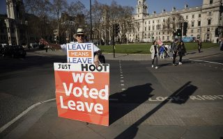 A leave the European Union supporter protests across the street from the Houses of Parliament in London, Wednesday, Feb. 27, 2019. British Prime Minister Theresa May says she will give British lawmakers a choice of approving her divorce agreement, leaving the EU March 29 without a deal or asking to delay Brexit by up to three months. (AP Photo/Matt Dunham)