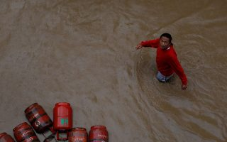 FILE PHOTO: A man walks past gas cylinders in a flooded colony in Kathmandu, Nepal July 12, 2019. REUTERS/Navesh Chitrakar/File Photo