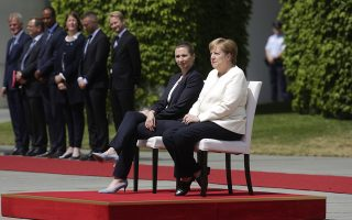 German Chancellor Angela Merkel, center right, and Danish Prime Minister Mette Frederiksen, center left, sit on chairs as they listen to the national anthems prior to a meeting at the chancellery in Berlin, Thursday, July 11, 2019. German Chancellor and the visiting Danish prime minister sit through their countries' national anthems at a ceremony in Berlin, a day after the latest of three incidents in which Merkel's body shook as she stood during the ceremony. (AP Photo/Markus Schreiber)
