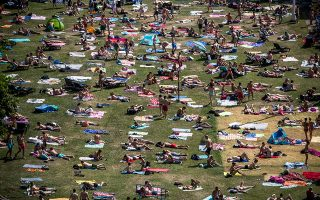 epa07674958 People sunbathe during warm weather on the grass of a public swimming pool in Prague, Czech Republic, 26 June 2019. As heat wave hits the Europe region, the Czech capital enjoyed a temperature around 37 degrees Celsius.  EPA/MARTIN DIVISEK