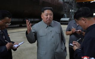 epa07734364 A photo released by the official North Korean Central News Agency (KCNA) on 23 July 2019 shows Kim Jong-Un (C), chairman of the Workers' Party of Korea, chairman of the State Affairs Commission of the Democratic People's Republic of Korea, and supreme commander of the armed forces of the DPRK, speaking to officials after making a round of the newly-laid down submarine at an undisclosed location in North Korea.  EPA/KCNA   EDITORIAL USE ONLY