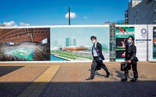 Δύο υπάλληλοι γραφείου περνούν μπροστά από τον φράχτη του Olympic Gymnastic Centre που είναι υπό κατασκευή, στην περιοχή Αριάκε του Τόκιο. Οι εικόνες αναπαριστούν πώς θα είναι στην τελική μορφή του. Φωτογραφίες: Ανδρονίκη Χριστοδούλου