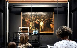 People look at Rembrandt's painting 'The Night Watch', protected by a glass barrier and video surveillance, as it undergoes public restoration after a first phase of study, in Rijksmuseum in Amsterdam, Netherlands July 8, 2019. REUTERS/Piroschka van de Wouw