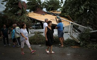 People stand next to a destroyed building where two people were fatally injured following heavy storms in the village of Nea Plagia, Greece, July 11, 2019. REUTERS/Alkis Konstantinidis