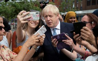 Britain's Prime Minister Boris Johnson takes a picture with a woman as he visits Birmingham, Britain July 26, 2019. Geoff Pugh/Pool via REUTERS
