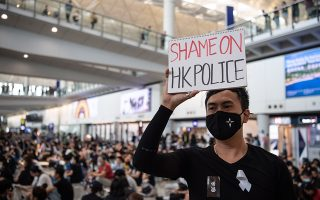 «Ντροπή για την αστυνομία του Χονγκ Κονγκ», αναγράφεται στην πικέτα διαδηλωτή στο αεροδρόμιο της πόλης.