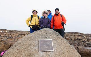 Επιστήμονες ποζάρουν δίπλα στην «επιτύμβια στήλη» του παγετώνα Οκγιεοκούλ, που εξαφανίστηκε.
