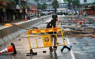 Διαδηλωτής κατασκευάζει οδόφραγμα σε κεντρικό δρόμο του Χονγκ Κονγκ.