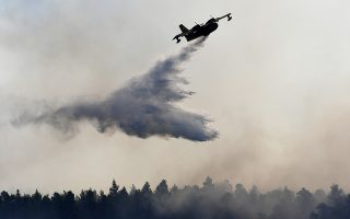 An airplane drops water over a wildfire near Halkida town on the Greek island of Evia, Wednesday, Aug. 14, 2019. More than a thousand firefighters battled wildfires Tuesday in Greece, with the largest burning out of control through a nature reserve on the island of Evia north of Athens causing four villages and a monastery to be evacuated. (AP Photo/Michael Varaklas)
