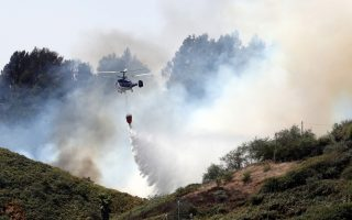 epa07780893 A firefighter helicopter pours a load of water on a forest fire in Santa Maria de Guia, Gran Canaria, Canary Islands, Spain, 19 August 2019. About 8,000 people have been evacuated from their houses as fire continues to burn land in the area since 17 August 2019. Approximately 6,000 hectares have burnt in the third fire in a week registered in the island.  EPA/ELVIRA URQUIJO A.