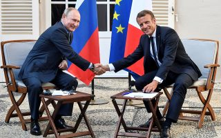 French President Emmanuel Macron shakes hands with Russia's President Vladimir Putin, at his summer retreat of the Bregancon fortress on the Mediterranean coast, near the village of Bormes-les-Mimosas, southern France, on August 19, 2019. Gerard Julien/Pool via REUTERS