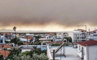 Ο καπνός από την πυρκαγιά στην Εύβοια μεταφέρθηκε στο λεκανοπέδιο, καλύπτοντας τον αττικό ουρανό.