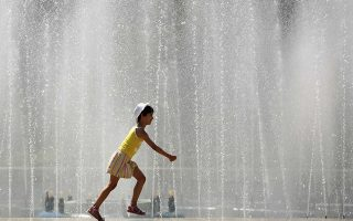 A child runs on the edge of a public fountain during a hot day in central Bucharest July 24, 2007. Twelve Romanians died over the past day as a week-old heatwave gripping southern parts of the Black Sea state drove temperatures to around 42 degrees Celsius, raising the total death toll to 30.  REUTERS/Bogdan Cristel (ROMANIA)