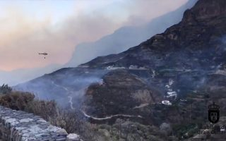 Houses dot the hillside as a helicopter flies to drop water over wildfires at Artenara, Gran Canaria, Canary Islands, Spain August 11, 2019 in this still image obtained from social media video. Twitter @CarreterasGC via REUTERS ATTENTION EDITORS - THIS IMAGE HAS BEEN SUPPLIED BY A THIRD PARTY. MANDATORY CREDIT. NO RESALES. NO ARCHIVES.