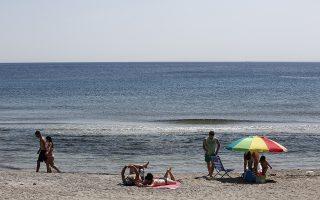 Κόσμος απολαμβάνει τον ήλιο και την θάλασσα σε παραλία στο Λαγονήσι, κοντά στην Αθήνα, Κυριακή 9 Ιουλίου 2017. Μία εβδομάδα μετά το πρώτο κύμα καύσωνα του φετινού καλοκαιριού, ένα ακόμη