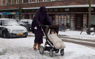 Μουσουλμάνα με νικάμπ βγάζει το μωρό της βόλτα στο Αμστερνταμ.