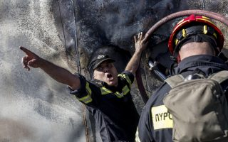 epa07769533 Firefighters try to extinguish a wildfire burning container boxes with telecommunication and radio equipment at the Radion Antenna Park atop of Ymmitos Mountain (Hymettus), after a wildfire that broke out at the foot of the mountain on the outskirt of Athens, Greece, 12 August 2019. A wildfire broke out in the forest of Paeania, suburb of Athens, was contained quickly by the fire brigade.  EPA/KOSTAS TSIRONIS