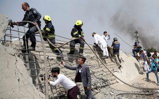Aφγανοί πυροσβέστες και δημοσιογράφοι ερευνούν τον τόπο της επίθεσης αυτοκτονίας στην Καμπούλ.