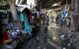 epa07872604 A Khlong Toei resident walks along a flooded unused rail track in Bangkok, Thailand, 12 September 2019 (issued 27 September 2019). Neighboring Bangkok's luxurious commercial district lies Khlong Toei community, the city's largest, housing over 70,000 residents who now face eviction. Often referred to as Thailand's largest slum, Khlong Toei's dwellers settled in about 320,000 square meters of land owned by the Port Authority of Thailand (PAT), who earlier this year announced plans to clear the land to make room for new luxury commercial and office developments. Within narrow alleys dotted with humble apartments and basic shacks, life in Khlong Toei is one of neighbors and families; families of mostly Thai migrants who came to the capital looking for work at the port nearly 70 years ago, today living community oriented lives, completely disconnected from their neighbor's wealthy lifestyles.  EPA/DIEGO AZUBEL  ATTENTION: This Image is part of a PHOTO SET