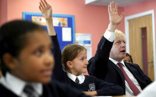 Britain's Prime Minister Boris Johnson, right, visits Pimlico Primary school in London, Tuesday July 10, 2018, to meet staff and students. (Toby Melville/Pool via AP)