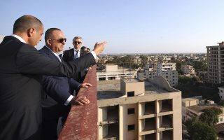 Kudret Ozersay, the foreign minister of the breakaway Turkish Cypriot north, left, speaks to Turkey's Foreign Minister Mevlut Cavusoglu, center, during a visit to the uninhabited Famagusta suburb of Varosha, in the breakaway, Turkish Cypriot north of ethnically split Cyprus on Monday, Sept. 9, 2019. The military guarded suburb has remained frozen in time since advancing Turkish troops seized it during Turkey's 1974 military intervention that came in the wake of a coup by supporters uniting Cyprus with Greece. (Turkish Foreign Ministry via AP, Pool)