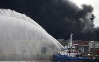 Firefighting vessel RMT Penfret sprays water as dark smoke billows in the sky after a large fire broke out at the factory of Lubrizol in Rouen, France, September 26, 2019. REUTERS/Pascal Rossignol