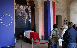 Visitors pay their respects at the coffin of late French President Jacques Chirac, Sunday, Sept. 29, 2019 at the Invalides monument in Paris. Jacques Chirac will lie in state Sunday during a public ceremony at the Invalides monument, where France honors its heroes. A memorial service and private funeral are planned for Monday. (AP Photo/Francois Mori)