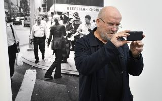 FILE - In this Feb. 2, 2017 file photo, Star photographer Peter Lindbergh takes pictures of the press with his phone in front of his street photography during the exhibition 'Women on Street' at the NRW Forum Gallery in Duesseldorf, Germany. Renowned German fashion photographer Peter Lindbergh has died Tuesday at the age of 74, his family announced. (AP Photo/Martin Meissner)