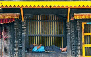 Ενας άνδρας κοιμάται έξω από βουδιστικό μοναστήρι στο Νεπάλ.