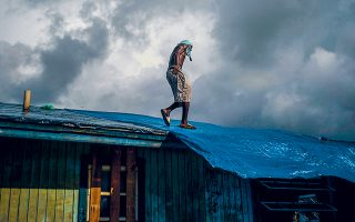 Στην κατεστραμμένη στέγη του σπιτιού του περπατά ο Τρέβον Λενγκ, μετά το πέρασμα του τυφώνα «Ντόριαν» από τις Μπαχάμες.