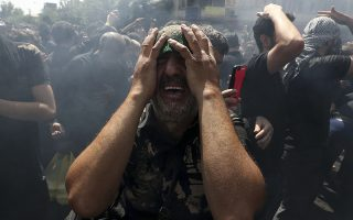 A Shiite Muslim mourns while actors re-enact the battle of Karbala in present-day Iraq in the 7th century during which Hussein, the grandson of Prophet Muhammad, and 72 of his companions were killed, in Ashoura commemoration in downtown Tehran, Iran, Tuesday, Sept. 10, 2019. Shiite Muslims around the world are observing Ashoura, one of the most sacred religious holy days for their sect. (AP Photo/Vahid Salemi)