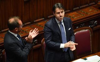 epa07830997 Italian Prime Minister, Giuseppe Conte (R), with the minister Alfonso Bonafede (L) celebrate after the vote of confidence to the new Government in the Chamber of Deputies, Rome, Italy, 09 September 2019. Italian Premier Giuseppe Conte presented his new government's programme in the Lower House ahead of the first of two confidence votes that the executive is set to face in parliament. His new government is a coalition between the anti-establishment 5-Star Movement (M5S) and the center-left Democratic Party (PD).  EPA/ALESSANDRO DI MEO