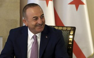 Turkish Foreign Minister Mevlut Cavusoglu smiles during a meeting with Turkish Cypriot leader Mustafa Akinci and with Turkish Cypriots leaders party in the Turkish occupied area in the northern part of divided capital Nicosia, Cyprus, Monday, Sept. 9, 2019. Cavusoglu is in the northern part of divided Cyprus for three-day visit. (AP Photo/Petros Karadjias)