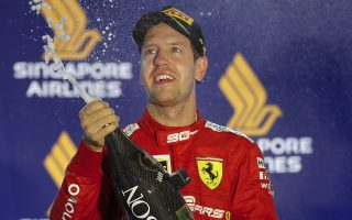 Ferrari driver Sebastian Vettel of Germany sprays champaign from the podium after winning the Singapore Formula One Grand Prix, at the Marina Bay City Circuit in Singapore, Sunday, Sept. 22, 2019. Leclerc finished second as Verstappen was third. (AP Photo/Vincent Thian)