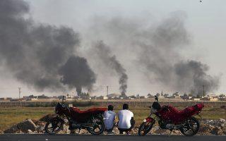 Μπούργκα μηχανής. Την θέα του πολέμου αγναντεύουν οι δυο κάτοικοι της περιοχής  Akcakale Sanliurfa της Τουρκίας. Μόνο που στην συγκεκριμένη περίπτωση το μάτι στην φωτογραφία πέφτει  στο  περίτεχνο στόλισμα των μηχανών τους με βελούδο και φούντες. (AP Photo/Emrah Gurel)