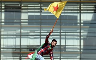 Κούρδος διαδηλωτής υψώνει σημαία έξω από το αρχηγείο του ΟΗΕ στη Βηρυτό, διαμαρτυρόμενος για την τουρκική εισβολή στη Συρία.