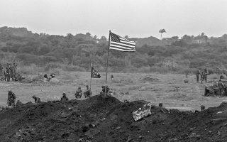 Ένα από τα τελευταία θερμά επεισόδια του Ψυχρού Πολέμου ξεσπάει στο μικροσκοπικό νησί της Γρενάδας, στην Καραϊβική, όταν μία δύναμη περίπου 7.600 ανδρών του αμερικανικού στρατού, συνεπικουρούμενη από 300 στρατιώτες αγγλόφωνων νήσων της Καραϊβικής, εισβάλει στο μικρό νησιωτικό κράτος, με σκοπό την ανατροπή της φιλοκουβανικής και φιλοσοβιετικής πραξικοπηματικής κυβέρνησης του Χάντσον Όστιν, το 1983. A.P./DOUG JENNINGS