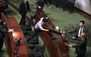 Security officers pursue pro-democracy lawmaker Au Nok-hin, center, as he leaps across desks to chase Hong Kong Chief Executive Carrie Lam as Lam leaves a question and answer session with lawmakers at the Legislative Council in Hong Kong, Thursday, Oct. 17, 2019. (AP Photo/Mark Schiefelbein)