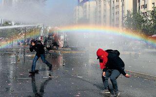 Το νερό που ρίχνει το όχημα της αστυνομίας για να διαλύσει διαδηλωτές στο Σαντιάγο της Χιλής σχηματίζει ουράνιο τόξο. Η διαρκής λιτότητα και η εκτόξευση των ανισοτήτων έχουν προκαλέσει την οργή του κόσμου. REUTERS/IVAN ALVARADO
