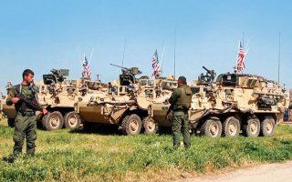 Κούρδοι μαχητές φρουρούν αμερικανικά άρματα μάχης στην Νταρμπασίγια της βόρειας Συρίας, τον Απρίλιο του 2017. Δυόμισι χρόνια αργότερα, η Ουάσιγκτον τους άφησε ανυπεράσπιστους απέναντι στην Αγκυρα. A.P. PHOTO