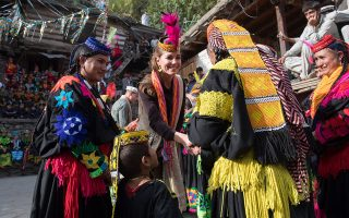 epa07925418 Britain's Catherine, Duchess of Cambridge (C) wears traditional Pakistani headwear as she visits a settlement of the Kalash people, to learn more about their culture and heritage, in Chitral, Pakistan, 16 October 2019. The British royal couple is on an official five-day visit to Pakistan.  EPA/SAMIR HUSSEIN / POOL
