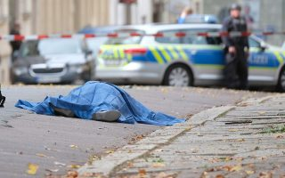 A person lies on a road in Halle, Germany, Wednesday, Oct. 9, 2019. A gunman fired several shots on Wednesday in German city of Halle and at least two got killed, according to local media FOCUS online.