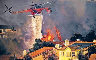 Ελικόπτερο ρίχνει νερό ενώ δίνει μάχη με τις φλόγες στο Σάντλεριτζ της Καλιφόρνιας. Η πυροσβεστική υπηρεσία του Λος Αντζελες έδωσε εντολή να εκκενωθεί περιοχή στην οποία κατοικούν 100.000 άνθρωποι, καθώς η φωτιά που ξέσπασε από το πρωί της Πέμπτης στις βόρειες παρυφές της πόλης ήταν εκτός ελέγχου.