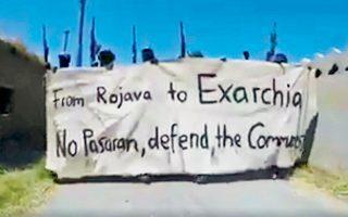 Στιγμιότυπο από βίντεο που ανήρτησε στο Διαδίκτυο ένοπλη αναρχική ομάδα στη Βόρεια Συρία. Τα μέλη της κρατούν πανό με σύνθημα «από τη Ροζάβα μέχρι τα Εξάρχεια προστατέψτε τις κομμούνες».