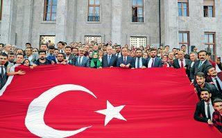 Ο Ταγίπ Ερντογάν και οπαδοί του απλώνουν μια τεράστια τουρκική σημαία, σε επίδειξη πατριωτισμού, μπροστά από το κτίριο της τουρκικής Εθνοσυνέλευσης, στην Αγκυρα.