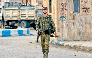 Μαχητής των παραστρατιωτικών που έχουν συμμαχήσει με την Τουρκία, σε έρημο δρόμο της Ταλ Αμπιάντ. Στο φόντο, αφίσα που εικονίζει τον Αμπντουλάχ Οτσαλάν.