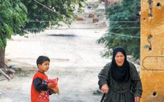 Μία ηλικιωμένη και ένα παιδί στην κατειλημμένη από τα τουρκικά στρατεύματα συριακή κωμόπολη Ρας αλ Αϊν.