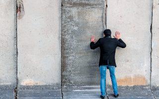 Ανδρας κοιτάζει μέσα από μια τρύπα, στο πλαίσιο της περφόρμανς «Κοιτάζοντας το Τείχος, ας το διαβούμε μαζί», στο Εθνικό Θέατρο της Βαϊμάρης.