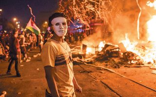 Μασκοφόρος αντικυβερνητικός διαδηλωτής στέκεται μπροστά από φλεγόμενο οδόφραγμα στο Σαντιάγο της Χιλής.