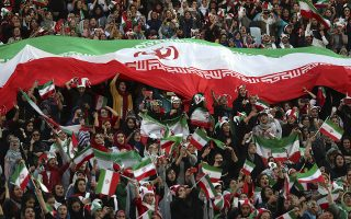 Iranian women cheer as they hold a huge Iranian flag during a soccer match between their national team and Cambodia in the 2022 World Cup qualifier at the Azadi (Freedom) Stadium in Tehran, Iran, Thursday, Oct. 10, 2019. Iranian women were freely allowed into the stadium for the first time in decades. The decision follows the death of a young woman who set herself on fire after hearing she could face prison time for sneaking into an Iranian soccer match disguised as a man. (AP Photo/Vahid Salemi)
